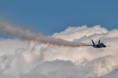 F/A-18 Hornet Blue Angel 7 descending from above with smoke trail and clouds..at the NAS Miramar Air Show in San Diego._TOM9026