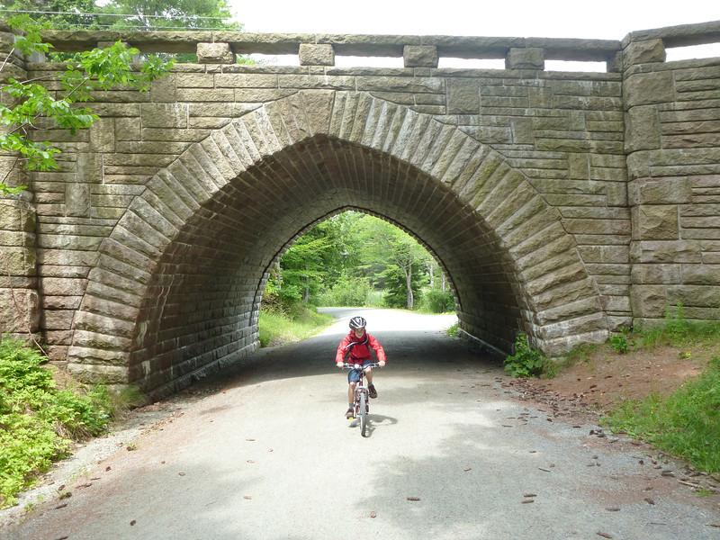 Drew riding his bike under one of the stone bridges