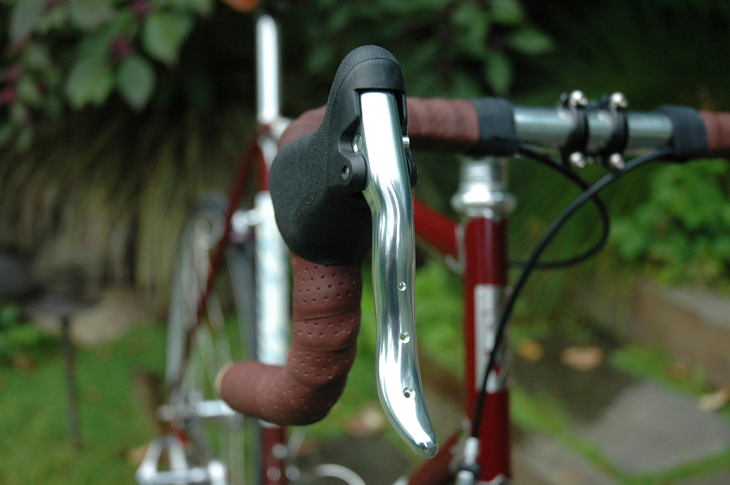 The brake levers are modern Tektros that Sacha drilled and polished for an old-school look.