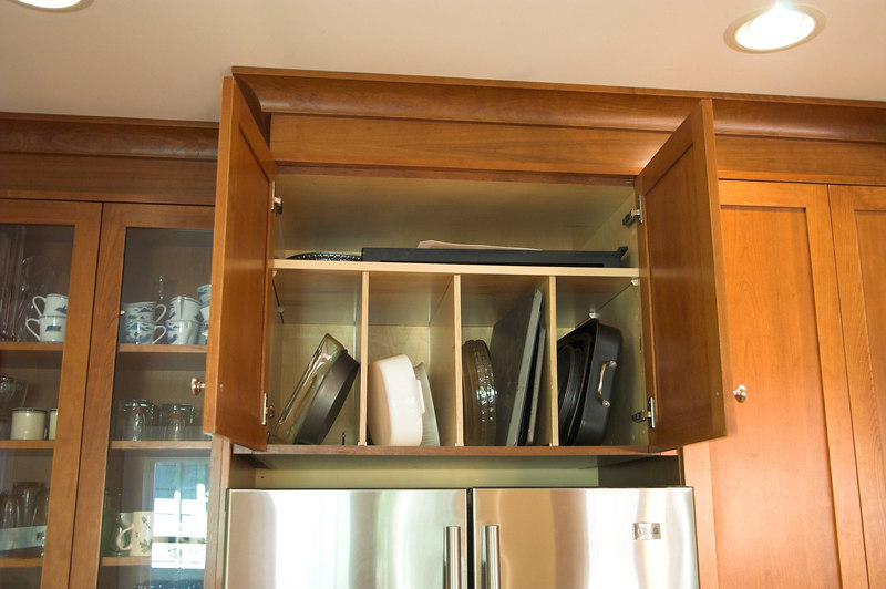 There is storage for baking dishes above the refrigerator.