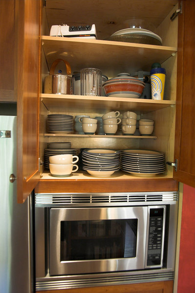 "This is the cabinet that replaced the old chimney.  The microwave is built in and also acts as a convection oven for baking.  The cabinet above is 24"" deep (twice as deep as a normal one) and holds almost all of our dishes.  We added a half depth shelf for easier access."