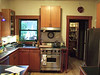 """A basic view of the old kitchen.  A few things to notice:<br /> * The wall cabinets are all of different heights<br /> * The range hood is not centered on the stove<br /> * There is just a small table to the right of the stove, not a cabinet.  It wasn't very sturdy.<br /> * The top drawers in the cabinets are very shallow (about 2.5"""" deep).  This made it difficult to fit much into them."""