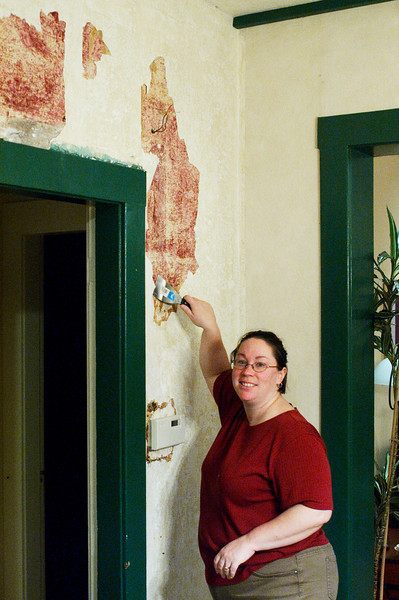 Christine removes plaster and wallpaper from the walls.