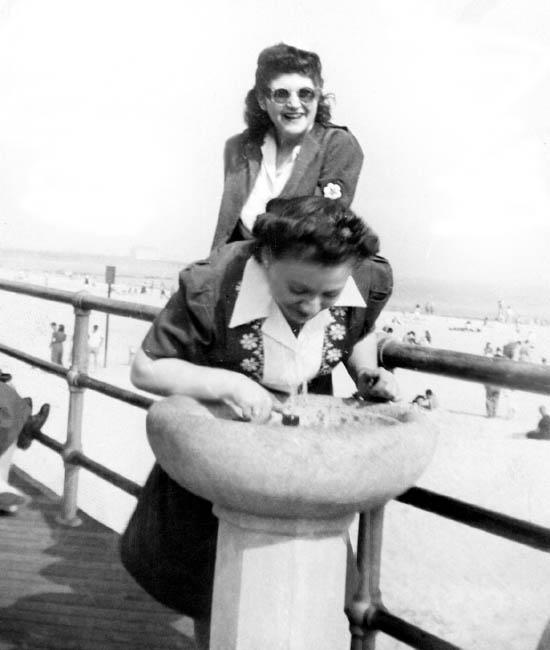 Bea Katz drinking at fountain.  Cynthia Schwartz in back