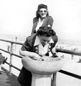 Bea Katz drinking at fountain on Boardwalk at Brighton Beach, in Brooklyn.  Cynthia Schwartz in back