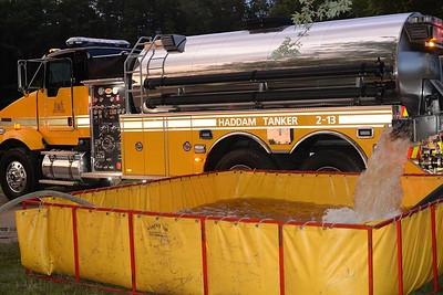 East Haddam Fire Department hosted a tanker shuttle drill on July 21, 2015. This drill included support from the surrounding mutual aid towns of Haddam, East Hampton, Haddam Neck and Lyme, which committed a total of five engines, four tankers and one ladder truck.  Tankers shuttled water from the fill site on the Moodus Reservoir causeway to four drop tanks at the East Haddam Town Beach, where the water was pumped to the ladder pipe, deck gun and hand lines. In the event of a structure fire in a rural town where hydrants are scarce, firefighters would use a similar process to deliver water to the structure fire. (Photo by Olivia Drake)