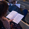 An audience member reads a prayer at the Sacred Song Service on Sunday, June 25, at the Amphitheater. OLIVIA SUN/STAFF PHOTOGRAPHER