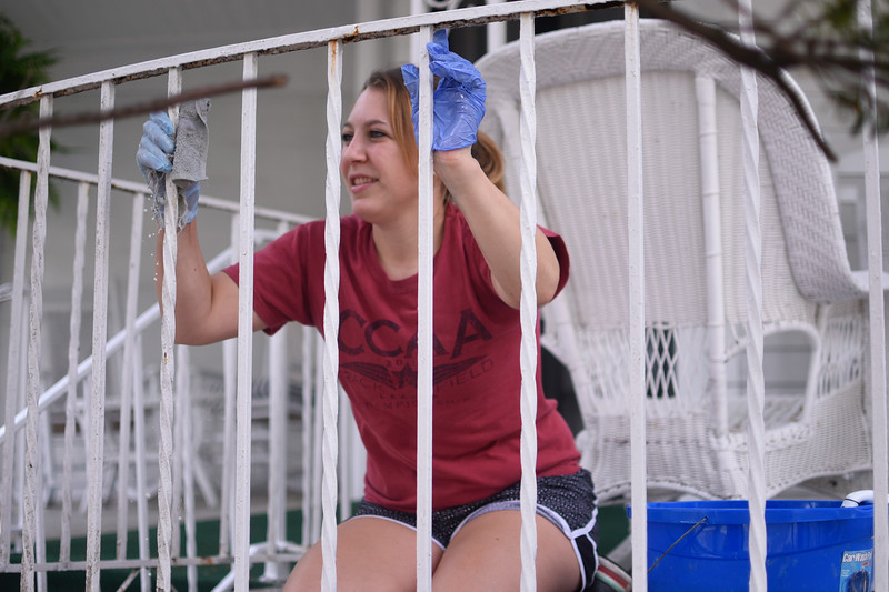 Kait White cleans a porch railing on Monday, June 19, 2017. OLIVIA SUN/STAFF PHOTOGRAPHER