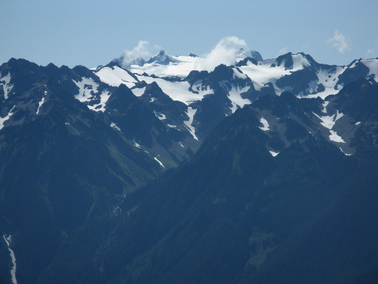 Mount Olympus in the center, with a wisp of cloud to the left of it.  Glaciers cover the higher reaches of the mountains surrounding it.