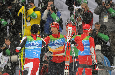 Johnny Spillane congratulates the gold medal Austrians after winning a silver medal for Team USA at Olympic Nordic Combined Team event. (U.S. Ski Team/Tom Kelly)