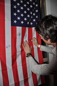 Johnny Spillane signs a US flag at the Spyder U.S. Ski Team House, Whistler, BC 2010 Olympic Winter Games ; beyond Photo: Katie Perhai/USSA