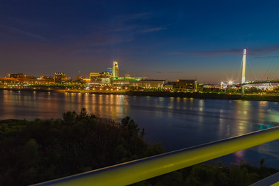 Blue hour night scene over downtown Omaha. The tallest building is the First National Bank of Omaha headquarters. The Convention Center is to the right. Beautiful skyline. Missouri River in the foreground. Beautiful Omaha Riverfront at the edge of Missouri River.