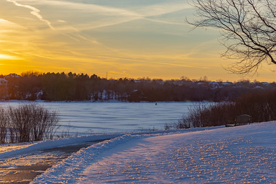 The empty bench. Sunset over frozen Ed Zorinsky lake with an empty bench along a cleared trail in the snow covered park. Ice fisherman on frozen lake.
