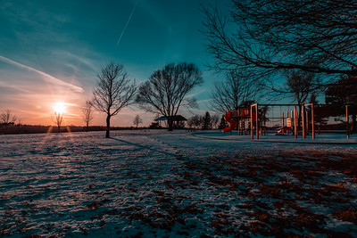 Sunset over a snow covered park land - Ed Zorinsky lake park. Trees are devoid of foliage. This is winter! Contrails in the sky.