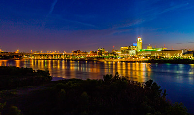 Blue hour night scene over downtown Omaha. The tallest building is the First National Bank of Omaha headquarters. The Convention Center is to the right. Douglas Street bridge to the left and Omaha Riverfront on the edge of Missouri River. Beautiful skyline and water reflections..