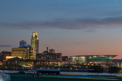 Blue hour sunset over downtown Omaha. The tallest building is the First National Bank of Omaha headquarters. The Convention Center is to the right. Beautiful skyline. Tom Hanafan River's edge plaza Council Bluffs Iowa and Missouri river in foreground.