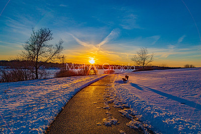The empty bench. Sunset over frozen Ed Zorinsky lake with an empty bench along a cleared trail in the snow covered park.