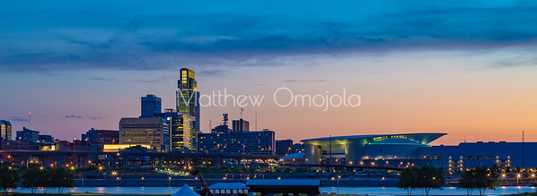 Blue hour sunset over downtown Omaha. The tallest building is the First National Bank of Omaha headquarters. The Convention Center is to the right. Beautiful skyline. Missouri river and Tom Hanafan plaza Council Bluffs Iowa in the foreground.
