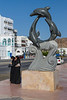 Muslim women and a decorative dolphin sculpture on the Corniche promenade in Muscat, Oman.