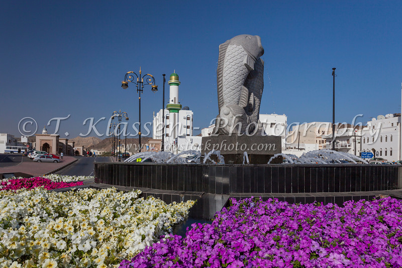 A two fish statue on a roundabout decorated with flowers in Muscat, Oman.