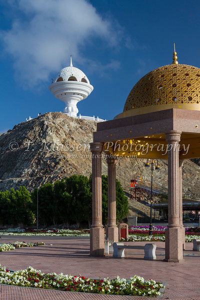 A gold dome cupola shelter and the incense burner landmark overlooking the Corniche promenade in Muscat, Oman.