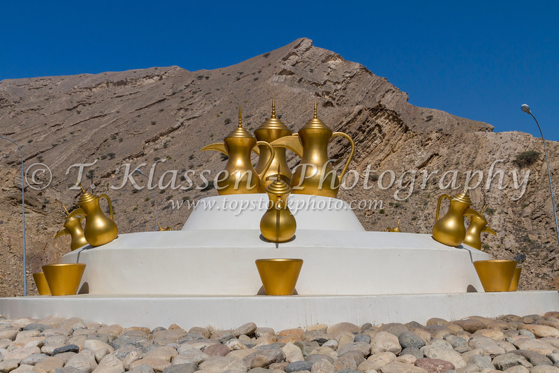Decorative gold coffee urns at a roundabout in Muscat, Oman.