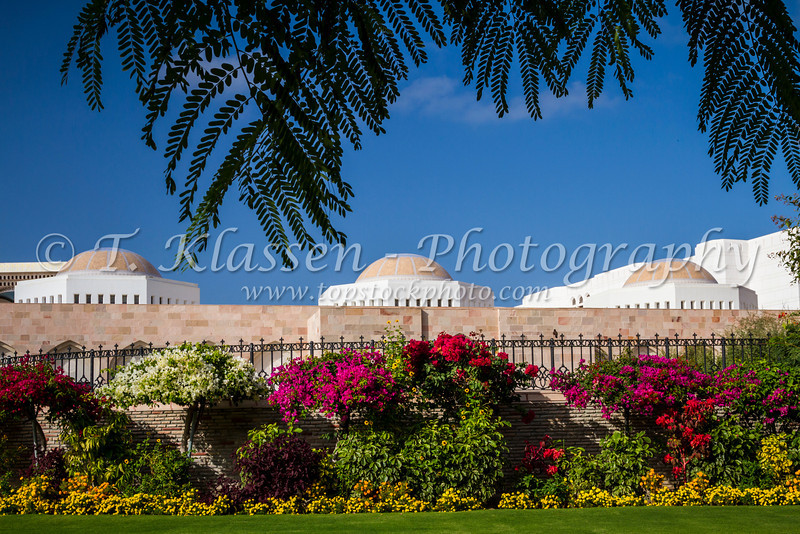 The Al Alam Royal Palace buildings with gardens and tropical foliage in Muscat, Oman.