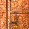 Detail of carvings on a traditional Arabian wooden door with lock.