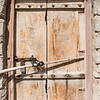 An old faded wooden door with carvings of the national symbol of Oman and rusted padlock.