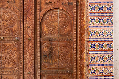 Detail of carvings on a traditional Arabian wooden door with lock and elaborately patterned tiles.