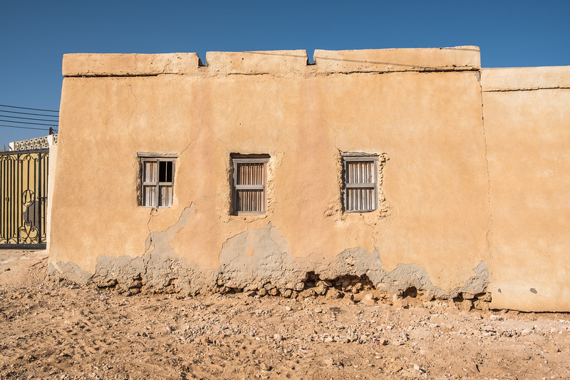 Windows with bars in the simple exterior adobe wall of a basic dwelling in a Middle Eastern village.