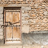 An simple faded wooden door with carvings of the national symbol of Oman in the stone wall of a simple dwelling with wooden lintel.