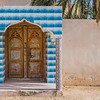 An elaborate entrance porch to an Arabian house with tiled porch and pillars and a finely carved wooden door.