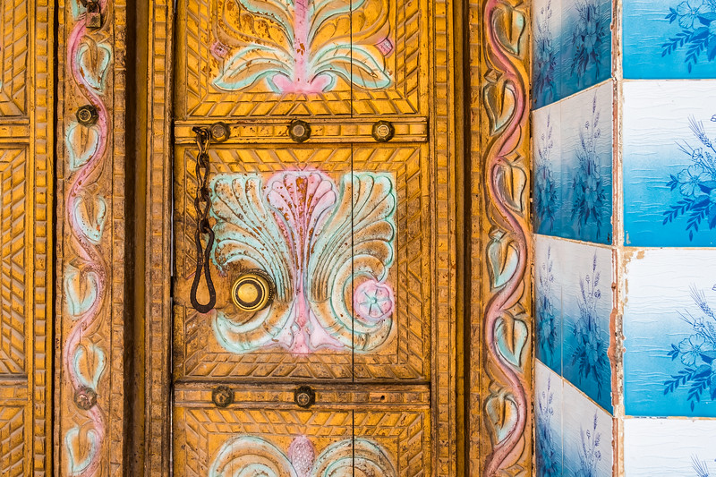 Detail of carvings on a traditional Arabian wooden door with lock and patterned tiles.