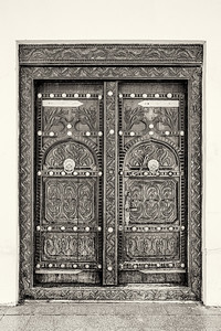 A black and white filtered view of a traditional eleborately carved Arabian house door with brass door knockers and large brass door nails.