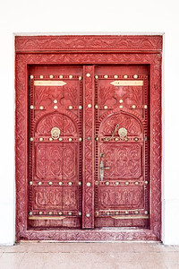 A traditional eleborately carved Arabian house door with brass door knockers and large brass door nails.