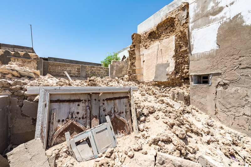 An old carved Arabian doorway lies buried in rubble from a demolished house.