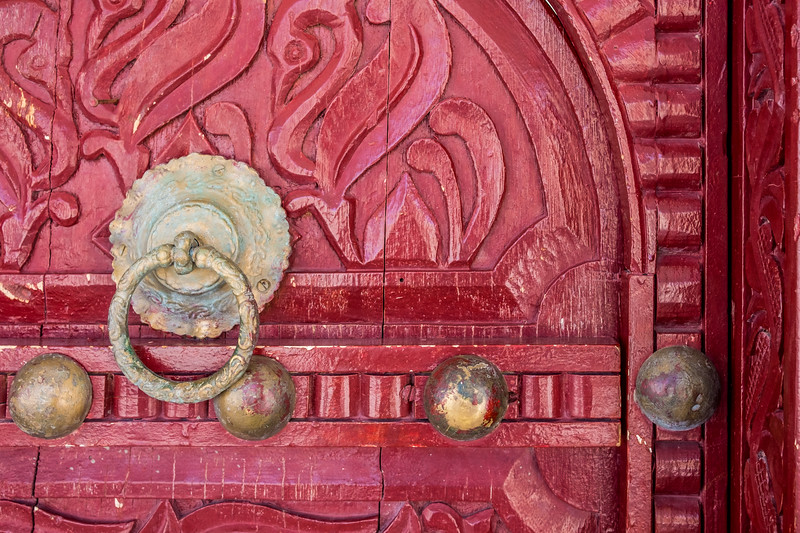 Detail of a traditional Arabian eleborately carved house door with a brass door knocker and large brass door nails.