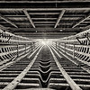 A black and white filtered view of the interior of a dhow or traditional Arabian sailing boat under construction.