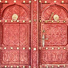 Detail of a traditional eleborately carved Arabian house door with brass door knockers and large brass door nails.