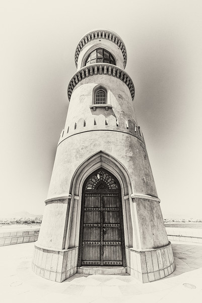 A wide-angle, filtered black and white view of the lighthouse in the suburb of Ayjah in the port of Sur, Oman.