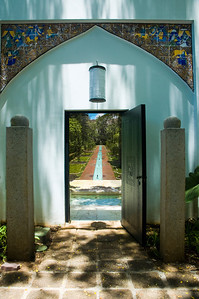 The Egyptian door opens to a Mughal  garden. There are geometric patterns within the long red brick pathways, the garden planters, and even in the waterfall that ripples down the marble steps.