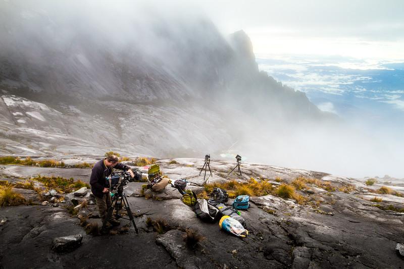 Camera operator Richard Kirby filming on the summit of Mount Kinabalu, Borneo