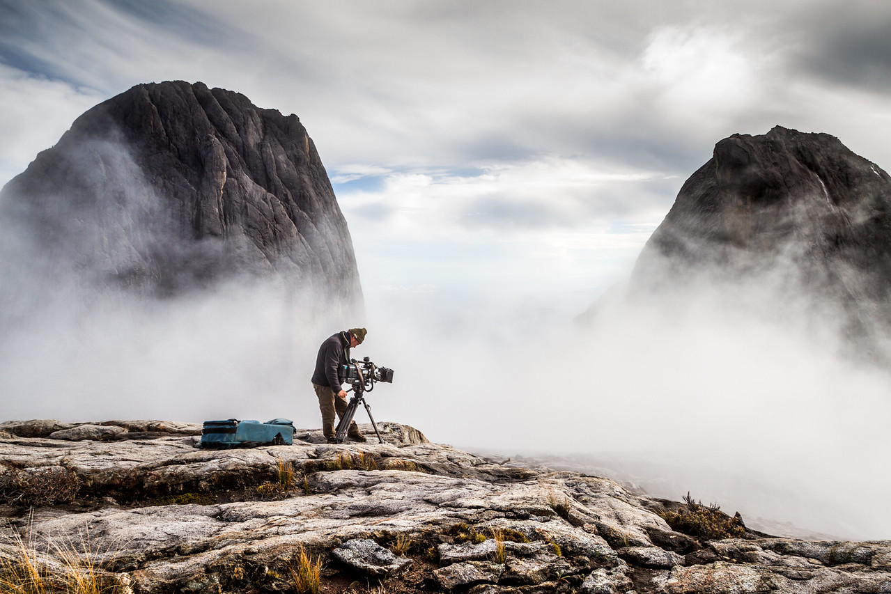 Cameraman Richard Kirby filming near the summit of Mount Kinabalu, Borneo. For the BBC series Wonders of the Monsoon.
