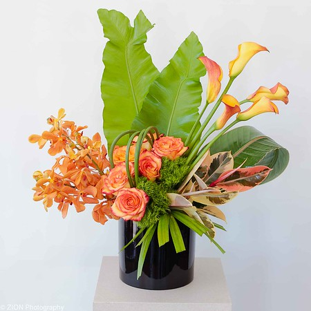 Calla lilies, roses and orchids with tropical leafs
