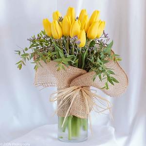 Yellow tulips in a glass vase wrapped in burlap