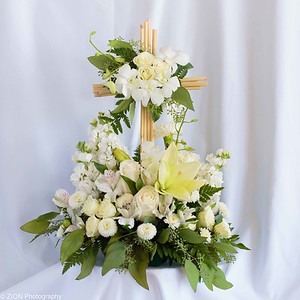 An assortment of white flowers with the Cross