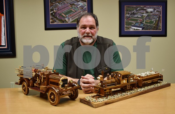 "Bob Myers of DeKalb poses with his replicas of Sycamore Fire Department's 1923 Stutz fire engine and of a locomotive nicknamed ""The Judge."""
