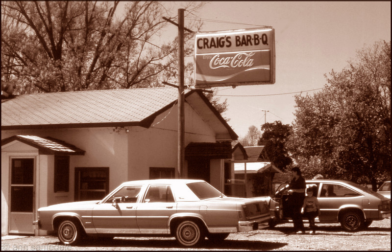 Craig's Bar-B-Q - De Valls Bluff, Arkansas - 1987. We stumbled on it int the Spring of 1987 by staying off the highway when driving through Arkansas east of Little Rock. Great pulled pork sandwiches.  Turns out it was and is a famous place. After congratulating ourselves on the find and savouring our BBQ we looked around the place to see the walls adorned with commendations from food critics.