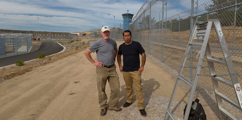 Michael O'Callahan and assistant Benjamin Galvez standing next to the Lethal Electrified Perimeter fence inside the maximum security unit of Folsom Prison SAC.  The assignment: photographing a prisoner-built Psychiatric Services Unit for Cannon Design Group.